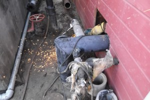 Hand cutting one of the pressure tank lines